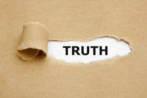 The word Truth appearing behind torn brown paper.