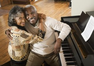 Senior African couple hugging next to piano
