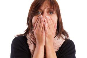 Frau ist entsetzt und hlt sich den Mund zu