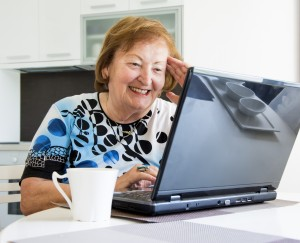 Elder woman at the computer searching the internet